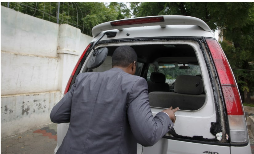 Abdiqadir Dulyar, director of Horn Cable, looks at the smashed window of a car that was carrying journalists working for his station, that unidentified gunmen opened fire on last week, in Mogadishu, Somalia. AP