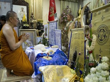 Chief monk at the Wat Traimitr Withayaram temple Phra Prommangkalachan prays in a room with Leicester City memorabilia in Bangkok, Thailand. AP