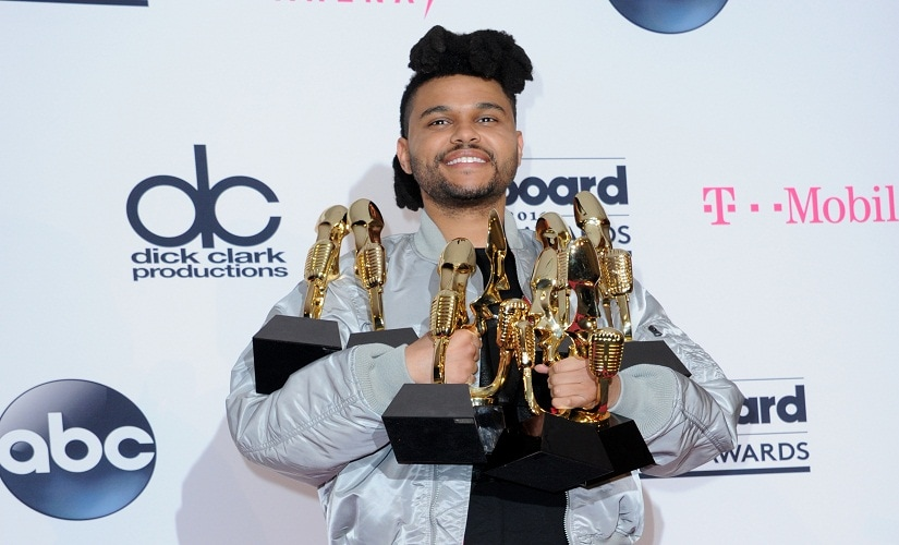 The Weeknd poses in the press room with his awards. Image from AP