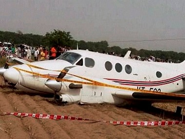 People watch the air ambulance which crash landed at Kair village in Najafgarh area of Delhi on Tuesday. PTI