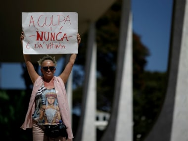 """Demonstrators attend a protest against rape and violence against women in Brasilia, Brazil on Sunday. Tha placard reads, """"Guilt is never of the victim"""". REUTERS"""