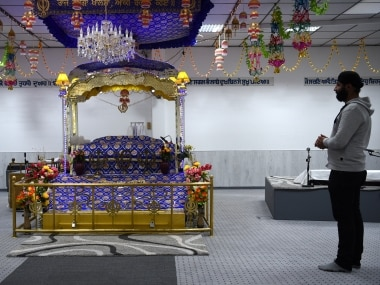 """A member of the Sikh community prays the Sikh temple, damaged by an explosion at the weekend can be seen in Essen, Western Germany on April 21, 2016. German police arrested two teenagers with Islamist backgrounds on April 21, 2016 over an explosion that wounded three people at a Sikh temple, labelling it a """"terrorist attack"""". / AFP PHOTO / PATRIK STOLLARZ"""
