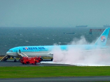 White smoke rises from an engine of a Korean Air jet as firefighters battle an apparent engine fire on the tarmac at Haneda Airport in Tokyo on Friday. PTI