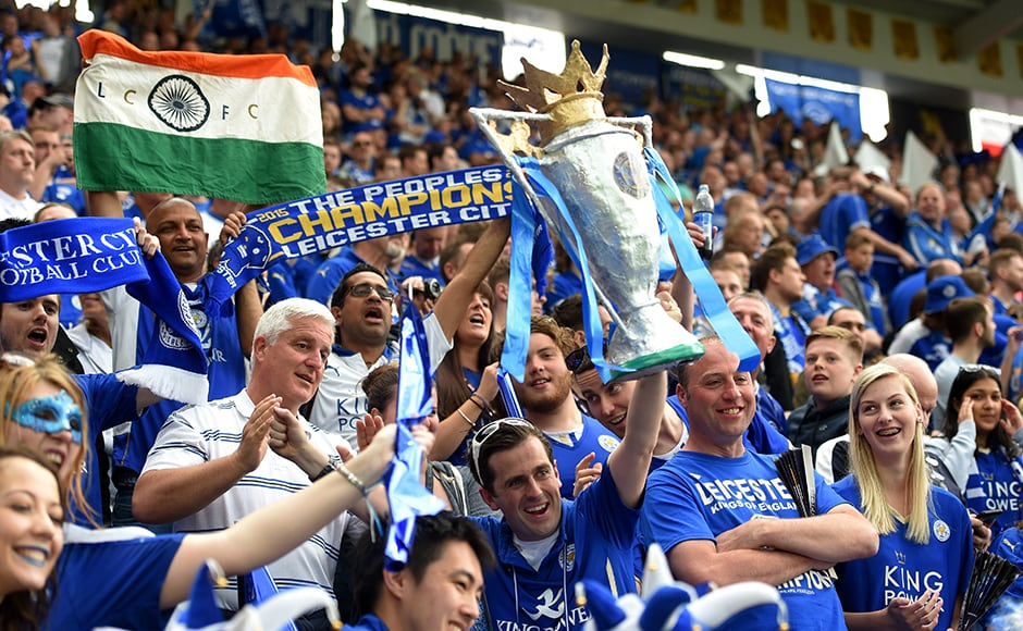 Leicester City supporters celebrate with trophy replicas. Getty