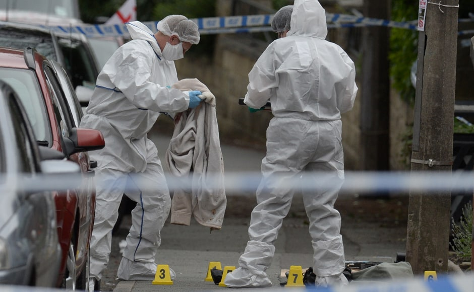A police forensic officer picks up a coat from the crime scene on the pavement outside the library in Birstall, northern England, where Labour MP Jo Cox was shot. British MP Jo Cox died from her injuries, police said, after being reportedly shot and stabbed in an attack in the street. AFP