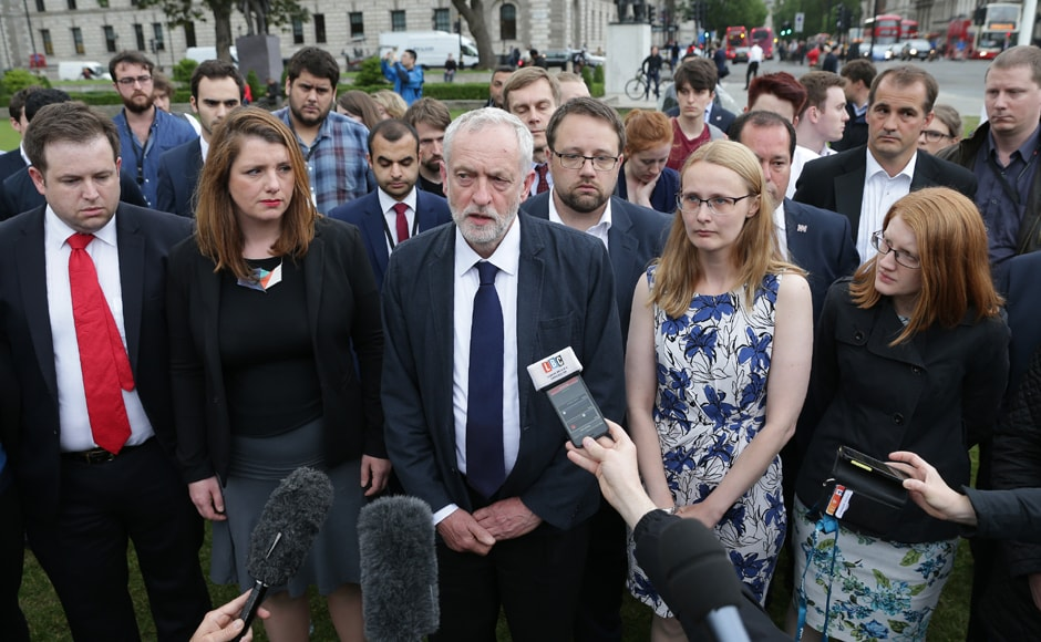 Labour leader Jeremy Corbyn (C) speaks to members of the press as he attends a vigil to slain Labour MP Jo Cox in Parliament square in London. AFP