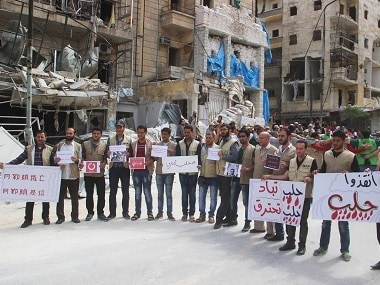 """Syrian activists hold Arabic placards that read, """"Save Aleppo, Aleppo burned, Aleppo is being wiped out,"""" during a sit-in in Aleppo, Syria. Civil Defense Directorate in Liberated Province of Aleppo via AP"""