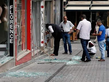 People stand outside their shops near the scene of the blast. AP
