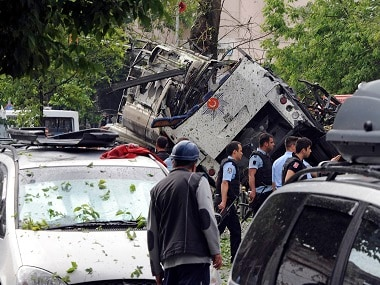 Turkish security officials and firefighters work at the explosion site after a bus carrying riot police official was struck by a bomb in Istanbul. DHA via AP