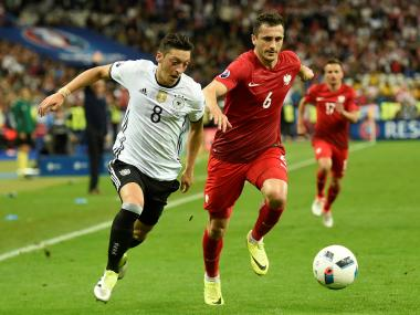 Germany's Mesut Ozil (L) vies for the ball against Poland's Tomasz Jodlowiec. AFP