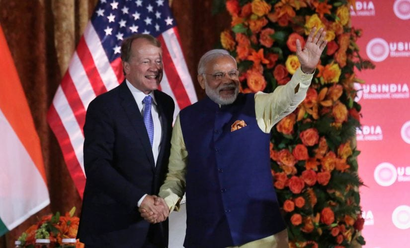Prime Minister Narendra Modi waves and shakes hands with USIBC chairman John Chambers. Reuters