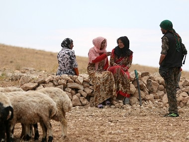 A fighter of the Syria Democratic Forces speaks with women in Haj Hussein village after SDF fighters took control of the village from Islamic State fighters, in the southern rural area of Manbij. Reuters