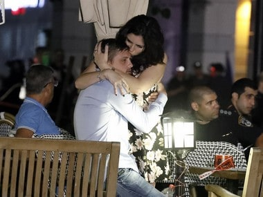 Israelis embrace following a shooting attack at a shopping complex in the Mediterranean coastal city of Tel Aviv on June 8, 2016. At least three people were killed and several wounded in the shooting spree, emergency services said. Police said that it appeared to be a militant attack, but they could not immediately give any details of the attacker or victims. AFP