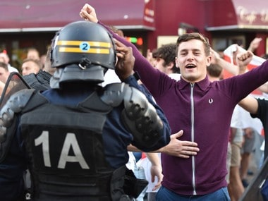 A French riot police officer talks to a football supporter in central Lille on June 15, 2016, during the Euro 2016 football championship. AFP