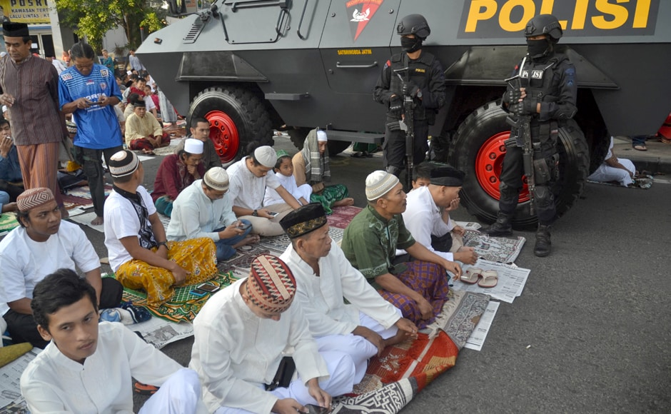 A group of Indonesian Muslims offers morning prayers under heavy police guard during Eid al-Fitr on the grounds of the Hati Kudus Jesus church in Malang, East Java as a show of solitarity and tolerance to the Christian faith. Indonesian Muslims are celebrating Eid with festivities and family reunions in the world's most populous Muslim-majority country at the end of the holy month of Ramadan. AFP