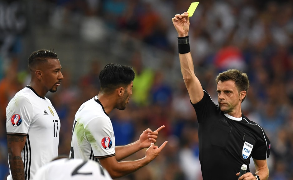 Italian referee Nicola Rizzoli gives a yellow card to Germany's defender Emre Can. AFP