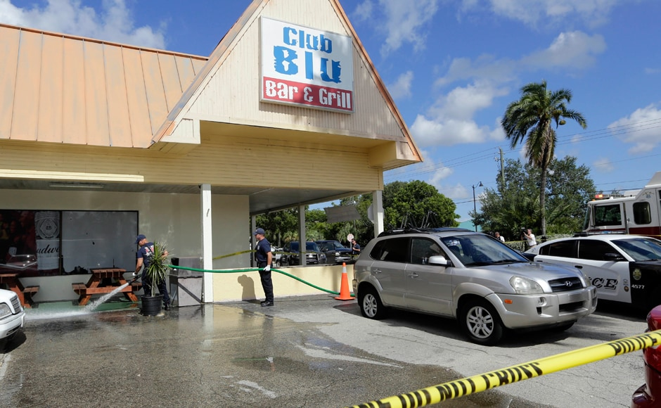 Fort Myers fire fighters hose down the pavement at the scene of a deadly shooting outside the Club Blu nightclub in Fort Myers, Fla., Monday, July 25, 2016. Police said the gunfire, which erupted at a swimsuit-themed party for teens, was not an act of terrorism. (AP Photo/Lynne Sladky)