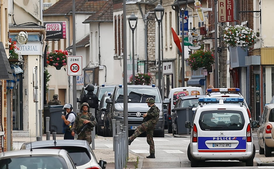 French soldiers stand guard near the scene of an attack in Saint-Etienne-du-Rouvray, Normandy, France, Tuesday, 26 July, 2016. Two attackers invaded a church Tuesday during morning Mass near the Normandy city of Rouen, killing an 84-year-old priest by slitting his throat and taking hostages before being shot and killed by police, French officials said. AP Photo/Francois Mori
