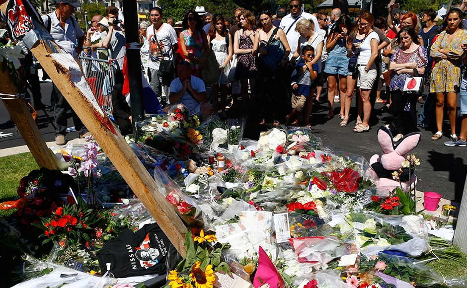 People gather by flowers laid near the scene where a truck mowed through revelers in Nice, southern France, Friday, on 15 July, 2016. AP