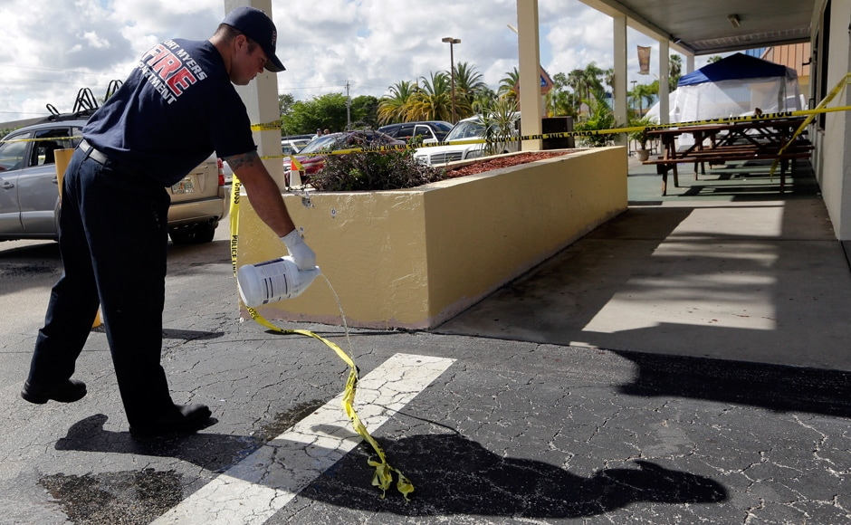 A Fort Myers fire fighter pours bleach over blood stains on the pavement at the scene of a deadly shooting outside the Club Blu nightclub in Fort Myers, Fla., Monday, July 25, 2016. Police said the gunfire, which erupted at a swimsuit-themed party for teens, was not an act of terrorism. (AP Photo/Lynne Sladky)