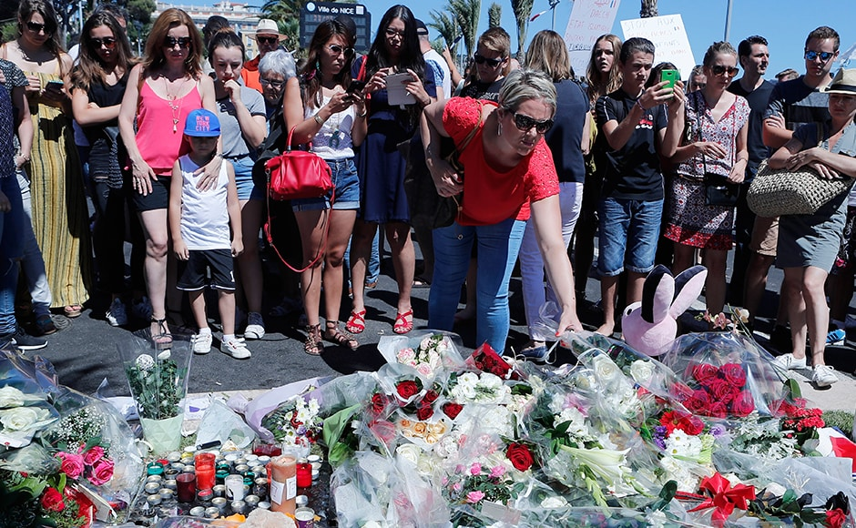 A woman puts flowers near the scene where a truck mowed through revelers in Nice, southern France, Friday, on 15 July, 2016. AP