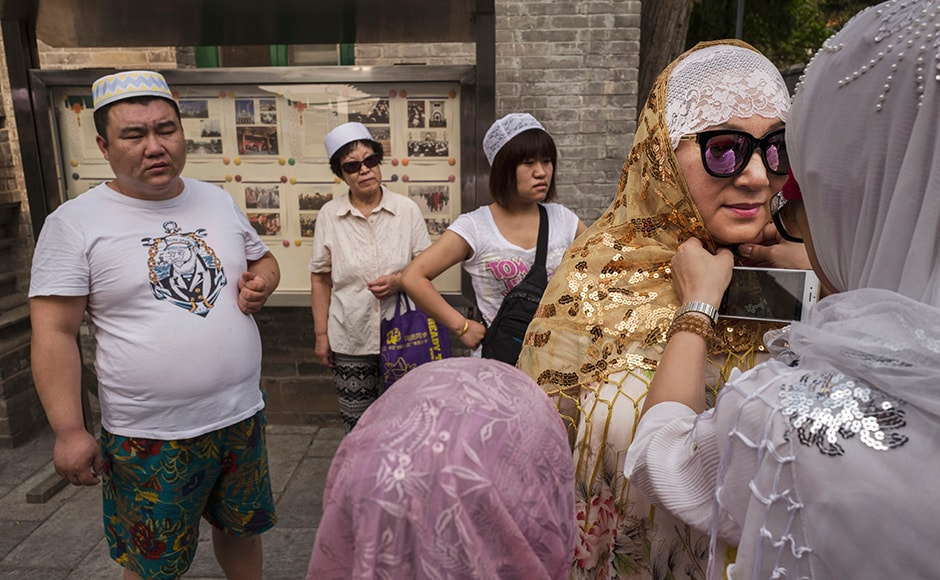 A Chinese Hui Muslim woman helps another with her headscarf before Eid prayers. Of an estimated 23 million Muslims in China, roughly half are Hui, who are ethnically Chinese and speak Mandarin. Getty images