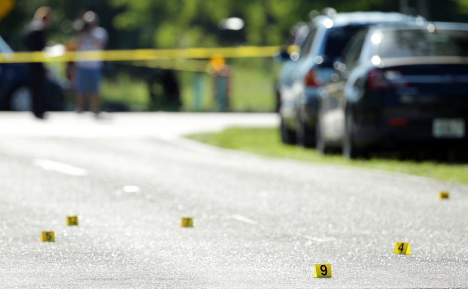 Evidence markers are placed on the street at the scene of a deadly shooting outside of the Club Blu nightclub, Monday, July 25, 2016, in Fort Myers, Fla. Gunfire erupted at the nightclub hosting a swimsuit-themed party for teens. (AP Photo/Lynne Sladky)