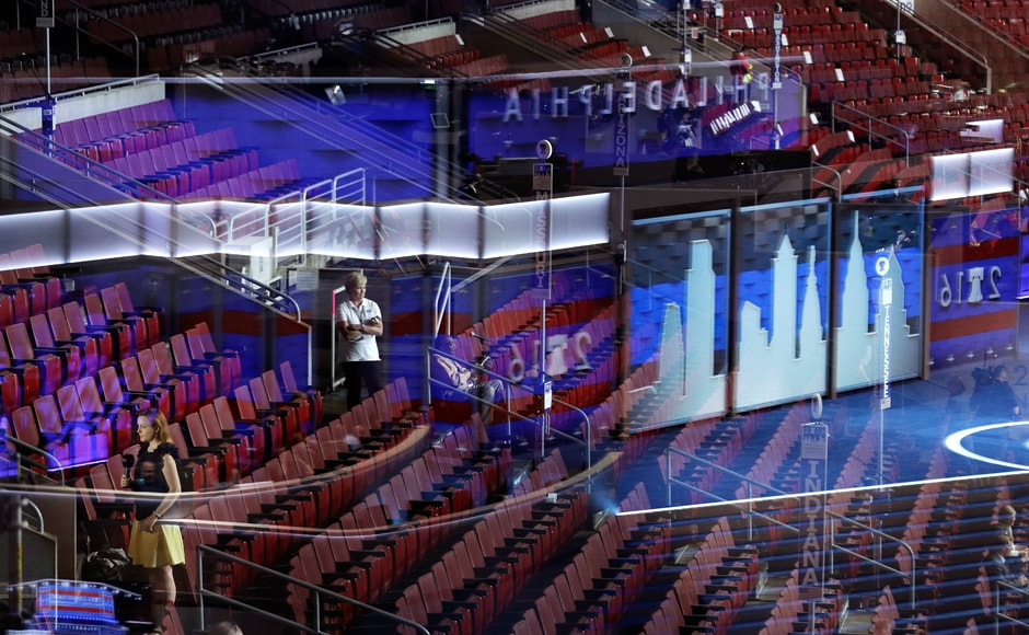 Seen through a reflection of the stage in a window, people stand in the seats during preparations for the DNC. The party announced Monday it would kick off its four-day spectacle with speeches from some of its most popular figures. Massachusetts Sen. Elizabeth Warren, a progressive favourite, would deliver the convention keynote. Sanders and First Lady Michelle Obama will also take the stage. AP