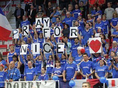"""French fans show """"Pray for Nice"""" banners to honor victims. AP"""