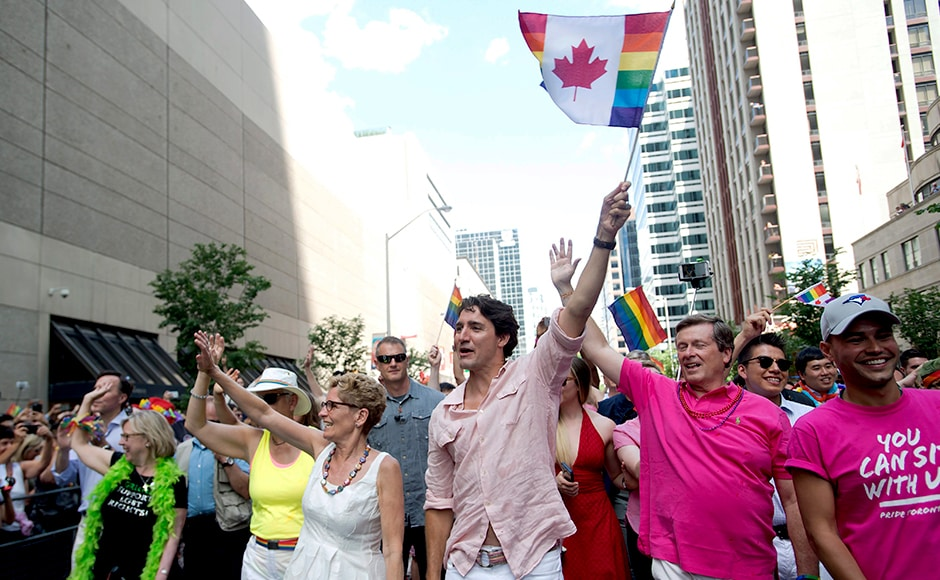 Thunderous applause greeted Trudeau as he paraded down a main Toronto artery, waving a Canadian maple-leaf flag bordered with a rainbow. Photo Courtesy: AP