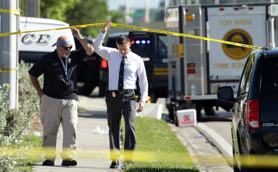 Officials investigate the scene of a deadly shooting outside of the Club Blu nightclub, Monday, July 25, 2016, in Fort Myers, Fla. Gunfire erupted at the nightclub hosting a swimsuit-themed party for teens. (AP Photo/Lynne Sladky)