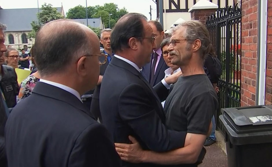 In this grab made from video, French President Francois Hollande, center, and Interior Minister Bernard Cazeneuve speaks with a local man after arriving at the scene of the hostage situation in Normandy, France, Tuesday, 26 July, 2016. Two attackers took hostages inside a French church during morning Mass on Tuesday in the Normandy town of Saint-Etienne-du-Rouvray, killing an 86-year-old priest by slitting his throat before being shot and killed by police, French officials said. The Islamic State group claimed responsibility for the attack. AP