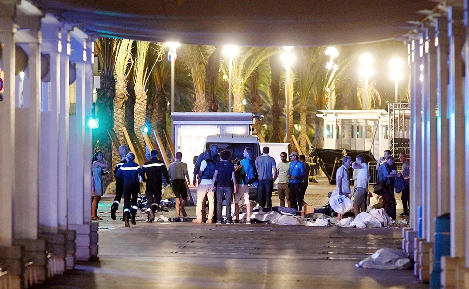 People stand next to covered bodies in the early hours of Friday, on 15 July, 2016, on the Promenade des Anglais in Nice, southern France. AP