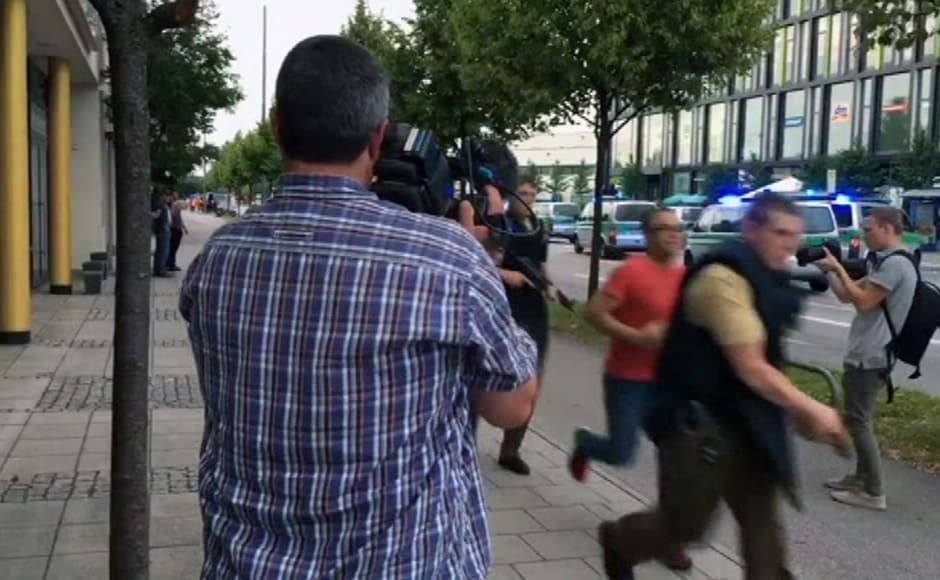 """Armed police responding to the shooting move past onlooking media. """"There is a major police operation under way in the shopping centre,"""" Munich police said on Twitter, urging people to avoid the area. AP/APTV"""