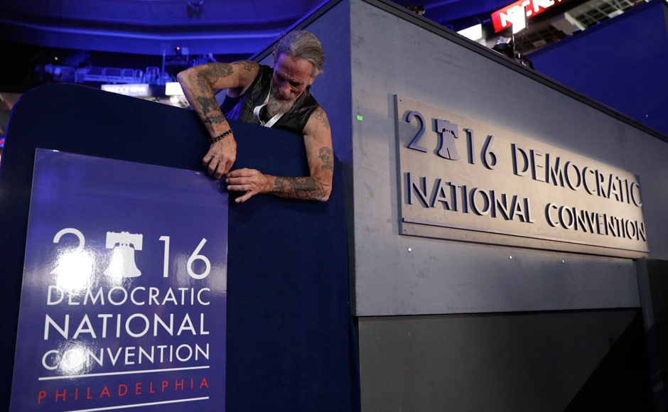 Gary Gort, a set carpenter with CNN, adjusts a sign during preparations before the 2016 Democratic Convention on Sunday in Philadelphia. The DNC begins on Monday at the Wells Fargo Center. AP