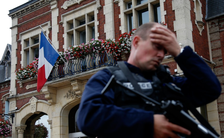 A policeman reacts as he secures a position in front of the city hall after two assailants had taken five people hostage in the church at Saint-Etienne-du -Rouvray near Rouen in Normandy, France, 26 July, 2016. Two attackers killed a priest with a blade and seriously wounded another hostage in a church in northern France on Tuesday before being shot dead by French police. Reuters/Pascal Rossignol