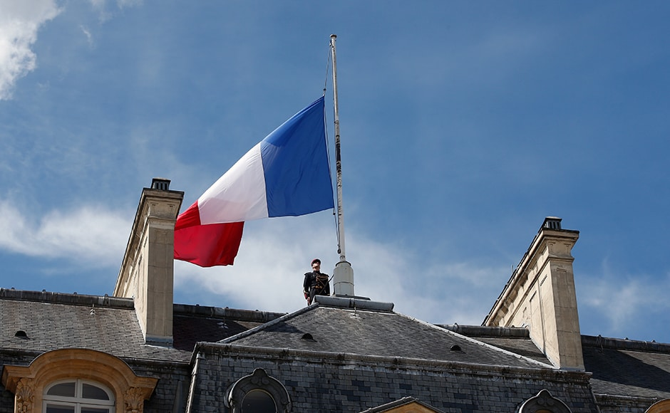 A soldier stands next to a half staff French flag, at the Elysee palace in Paris, Friday, 15 July 2016. French Prime Minister Manuel Valls said the government is declaring three days of national mourning after the attack in Nice that left at least 84 people dead. AP
