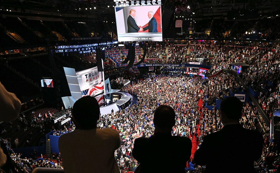 People watch a television monitor from the upper seats as Donald Trump shakes hands with Mike Pence at the Republican National Convention in Cleveland, Ohio. Trump had earlier announced that Pence would be his running mate as the race for the US Presidential election 2016 heats up in earnest. Reuters