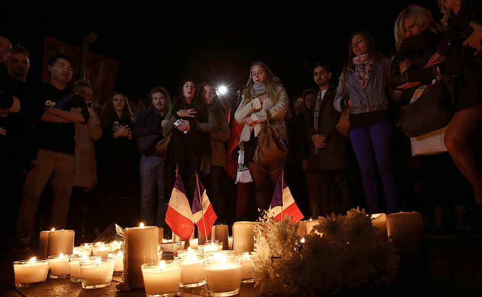 People stand around a circle of candles during a moment of silence at a vigil to honour victims of the Bastille Day tragedy in Nice, France, in Sydney on 15 July, 2016. AP