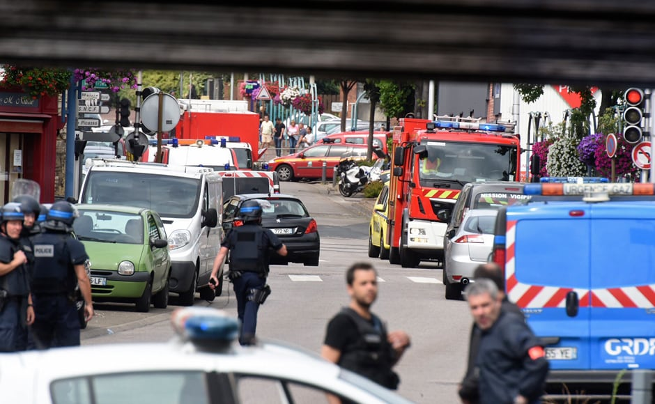 Police and rescue workers stand at the scene after two assailants had taken five people hostage in the church at Saint-Etienne-du -Rouvray near Rouen in Normandy, France, 26 July, 2016. Two attackers killed a priest with a blade and seriously wounded another hostage in a church in northern France on Tuesday before being shot dead by French police. Reuters/Steve Bonet