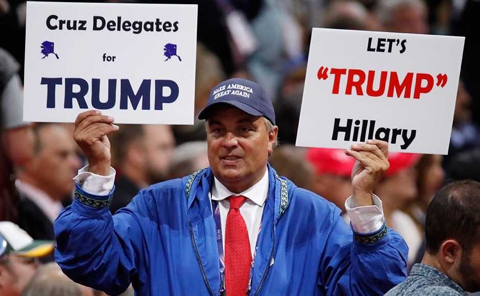 """A delegate holds a sign calling for Ted Cruz delegates to support Donald Trump in order to defeat Hillary Clinton. The most popular memorabilia on sale in Cleveland were those targeting Clinton. """"Hillary for Prison 2016"""" is emblazoned on perhaps the most popular T-shirt promoting a rising negative campaign to characterise the Democratic Party's presidential hopeful as a criminal. Reuters"""