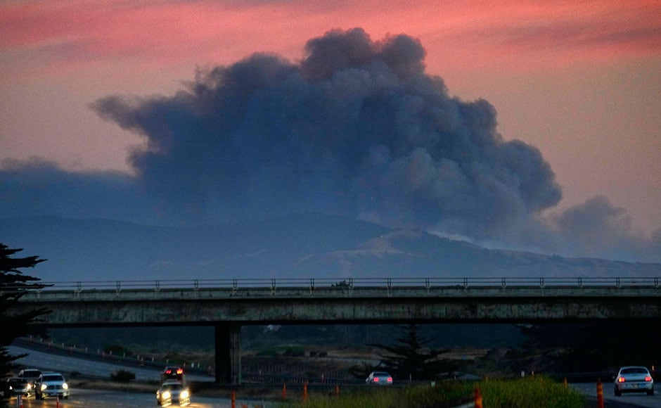 A large plume of smoke from a wildfire rises near Highway 1, burning five miles south of Carmel, California, on  22 July. AP