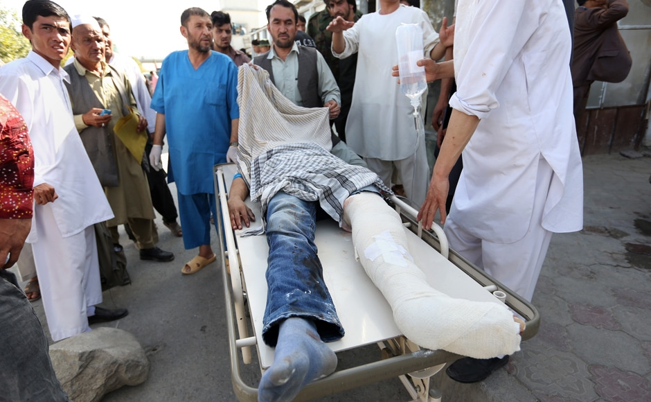 Afghans help an injured man after an explosion struck a protest in Kabul, Afghanistan, Saturday, July 23, 2016. Witnesses in Kabul say that an explosion struck the protest march by held largely by members of Afghanistan's Shiite Hazara ethnic minority group, demanding that a major regional electric power line be routed through their impoverished home province. AP