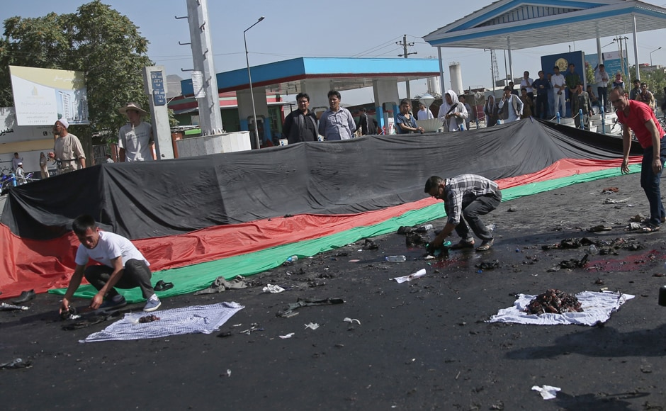 Afghans gather property, left behind by victims of a deadly explosion that struck a protest march by ethnic Hazaras, in Kabul, Afghanistan, Saturday, July 23, 2016. The protesters on Saturday were demanding that a major regional electric power line be routed through their impoverished home province. AP