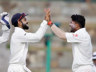 Umesh Yadav celebrates with captain Virat Kohli after taking a wicket. AP