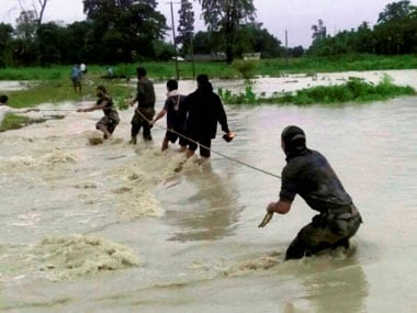 Indian Army soldiers rescue flood affected villagers near India-Bhutan border of Chirang district in Assam on Friday. PTI