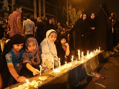 People light candles at the scene of a massive car bomb attack in Karada. AP