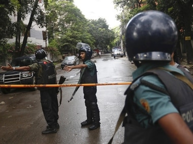 Policemen clear area outside the bakery in Dhaka, where gunmen killed 20 foreign nationals on Friday. AP
