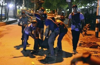 People help an unidentified injured person after a group of gunmen attacked a popular restaurant in Dhaka. AP