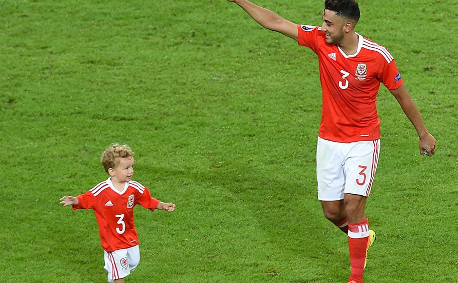 Neil Taylor celebrates with his son Marley on field as wales qualified for their first major semi-final. AFP
